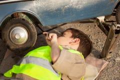更换在一辆老玩具汽车的年轻男孩一个轮胎 图库摄影
