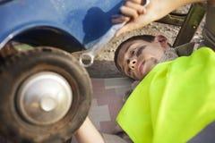 更换在一辆老玩具汽车的年轻男孩一个轮胎 免版税库存图片