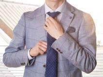 换衣服为工作的无法认出的商人,调整他的领带 与透镜火光的软的颜色 免版税库存图片