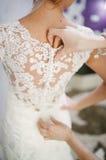 换衣服在她的婚礼之日的新娘 免版税库存照片