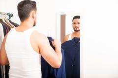 换衣服在镜子前面的人 图库摄影