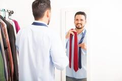 换衣服在镜子前面的年轻人 库存照片