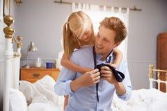 换衣服的女儿帮助的父亲为工作 库存图片