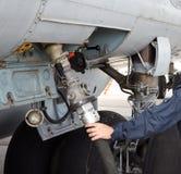 换装燃料飞机的过程在机场 插入燃料油管 免版税库存照片
