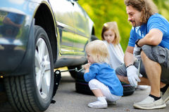 更换车轮的小女孩帮助的父亲 库存照片