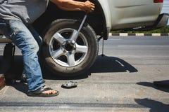 更换轮子的一个人 免版税图库摄影