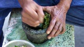 捣许多在石灰浆的新鲜的草本的一只男性手 影视素材