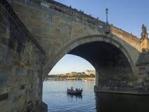 捷克,布拉格, 2018年9月8日:有航行在查尔斯在伏尔塔瓦河河,金黄小时的桥梁弧下的旅游人民的小船 免版税库存图片