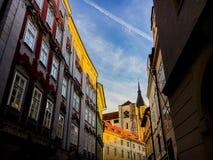 捷克,布拉格2017年12月26日:与一个塔和时钟的建筑学通过为圣诞节装饰的古老街道 免版税库存图片
