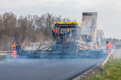 捷克,比尔森, 2016年4月10日, :在修路和修理期间的工作者经营的沥青摊铺机机器运转 免版税图库摄影