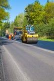 捷克,比尔森, 2016年5月7日, :涂柏油传播的机器和振动路辗在路面道路工程 图库摄影