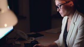 掀动下来后研究计算机的被射击俏丽的年轻女商人在键入使用键盘的晚上坐在书桌 股票录像