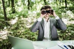 掀动年轻商人的图象使用双筒望远镜在露天的办公室 公执行委员搜寻机会以绿色 库存图片
