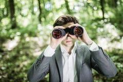 掀动年轻商人的图象使用双筒望远镜在露天的办公室 公执行委员搜寻机会以绿色 免版税库存图片