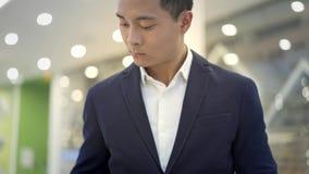 掀动突然上升了在衣服的亚洲男性商人与在他的膝盖的膝上型计算机一起使用