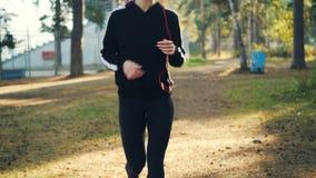掀动被射击教练员的俏丽的少女和田径服跑步在公园佩带的耳机的和享用物理 影视素材