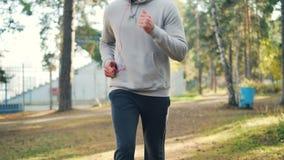 掀动跑步在公园佩带的耳机和享受体育活动的被射击教练员的帅哥和田径服 影视素材