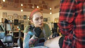 掀动年轻红发在女孩客户的腿的妇女纹身花刺艺术家刺字的图片射击在演播室 影视素材
