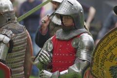 授以爵位在钢装甲,拿着在作战的手剑 免版税库存图片