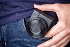 去掉一台袖珍照相机的人在口袋外面 免版税库存图片