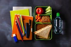 去掉食物有三明治水和学校用品的午餐盒 免版税库存图片