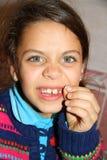 掉他的第一颗牙的逗人喜爱的孩子画象 免版税图库摄影