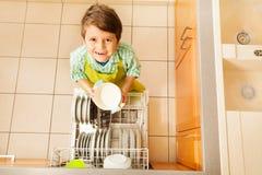 去掉从洗碗机的愉快的孩子男孩盘 库存照片