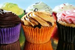 排列五颜六色的奶油色杯形蛋糕松饼 免版税库存图片