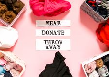 排序在捐赠,佩带和放弃的家庭衣橱的衣裳与关于软的桃红色背景的纸笔记 衣物项目 库存图片