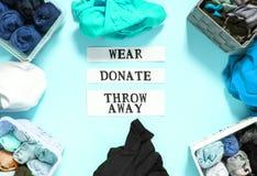 排序在捐赠,佩带和放弃的家庭衣橱的衣裳与关于软的桃红色背景的纸笔记 衣物项目 免版税库存照片