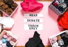 排序在捐赠,佩带和放弃的家庭衣橱的衣裳与关于软的桃红色背景的纸笔记 库存照片