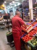 排序新鲜蔬菜的雇主在超级市场 库存照片
