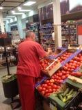 排序新鲜蔬菜的雇主在超级市场 免版税库存照片