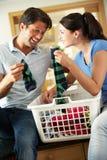 排序洗衣店的夫妇在厨房里 免版税库存照片