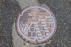 排泄下水道盖子表面上的盖帽艺术在步行途中的白川町去 免版税库存图片