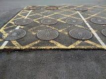 排泄在街道上的金属盒盖,黄色和空白线路 图库摄影