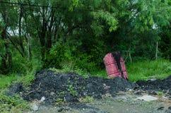 排泄黑垃圾液体的桃红色桶 免版税库存照片