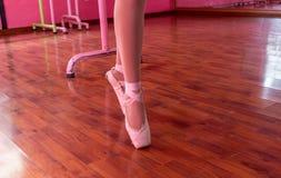 排练与芭蕾她的桃红色拖鞋的芭蕾舞女演员  免版税库存图片