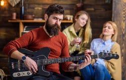 排练新的展示的吉他弹奏者 招待他的妻子和女儿有可爱的声调的有胡子的人 岩石音乐家 免版税图库摄影