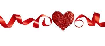 排行与红色丝绸扭转的丝带的安排并且闪烁心脏 库存图片