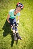 直排轮式溜冰鞋的适合的成熟妇女在草 免版税图库摄影