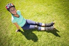 直排轮式溜冰鞋的适合的成熟妇女在草 免版税库存照片
