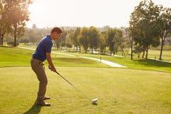 排队发球区域的男性高尔夫球运动员射击在高尔夫球场 免版税库存照片