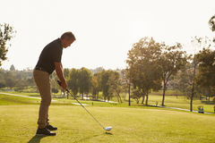 排队发球区域的男性高尔夫球运动员射击在高尔夫球场 库存照片
