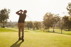 排队发球区域的男性高尔夫球运动员射击在高尔夫球场 图库摄影