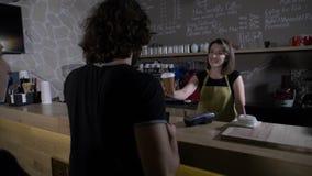 排队在咖啡馆的客户购物服务并且支付与在他们的流动智能手机实施的一种新技术app - 股票视频