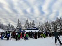 排队小组的滑雪者和的挡雪板搭滑雪电缆车的便车在赛普里斯山 免版税库存照片