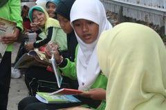 排队的学生读一本书在流动图书馆里 免版税库存图片