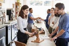 排队的顾客预定和支付在咖啡店柜台 库存图片