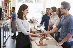排队的顾客预定和支付在咖啡店 免版税库存图片